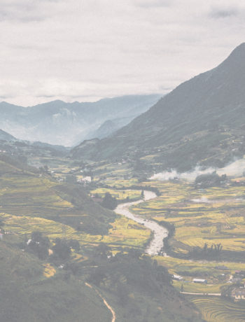 image of a river winding through a valley with mountains in the background